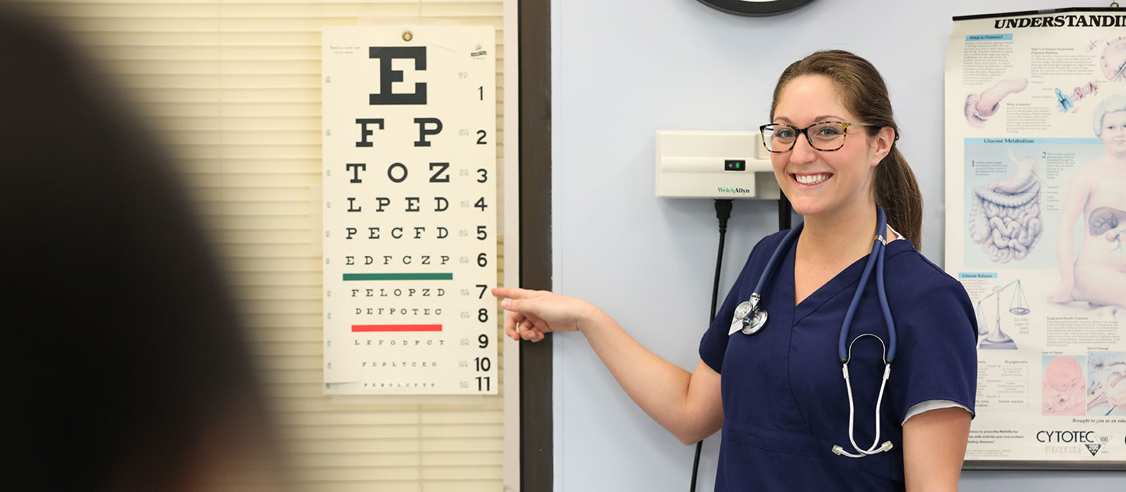 Student pointing at eye chart
