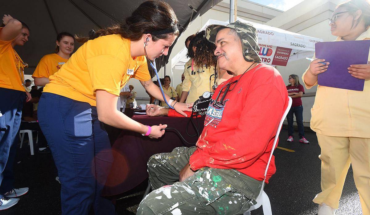 A nursing student takes a patient's blood pressure